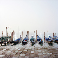 Gondolas moored on a misty day in Venice, Italy