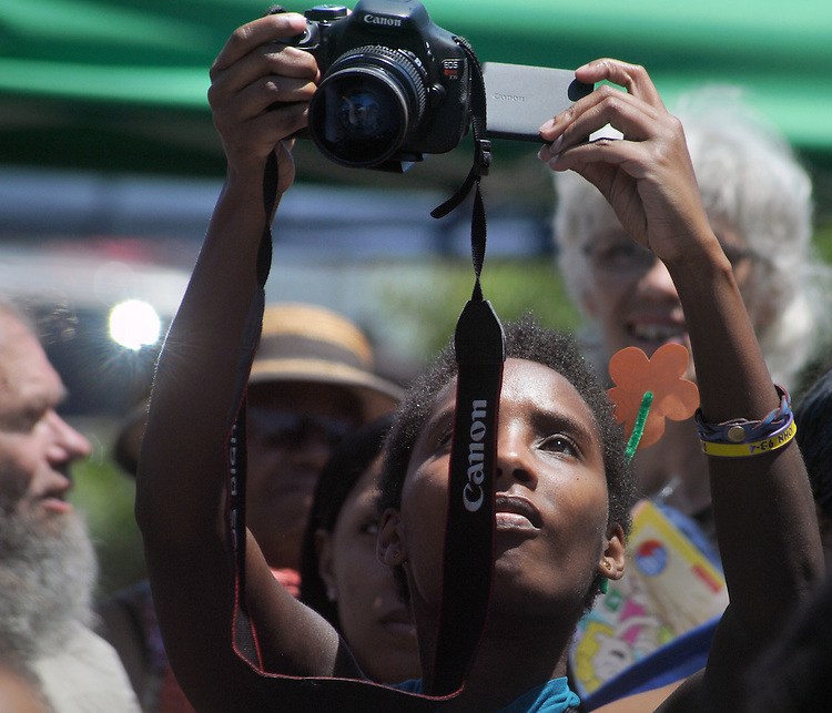 Close-up of a local Photojournalist at work covering the 11th Annual Mid-town Make a Difference Day Celebration on Franklin Street, in Kingston, NY on Saturday, June  18, 2016. Photo by Jim Peppler. Copyright Jim Peppler 2016.