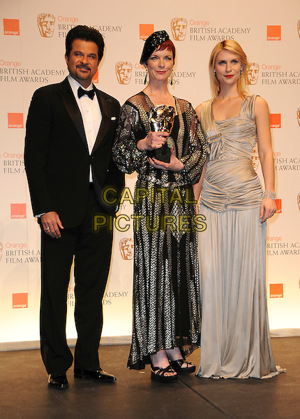 """ANIL KAPOOR, SANDY POWELL & CLAIRE DANES .pose with winner Sandy Powell for Best Costume, for the film """"The Young Victoria"""".The Orange British Academy Film Awards 2010 at the Royal Opera House Covent Garden, London, England, UK,.February 21st, 2010 .press awards room pressroom BAFTA BAFTAs full length black sequined hat sequin gold tuxedo tux long maxi sheer dress sandals platform ruched grey gray beige Burberry dress funny Clare trophy award belt beret bow tie .CAP/CAS.©Bob Cass/Capital Pictures"""