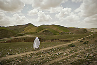 A woman wearing a white burqa walks along a path through the hills. The grass is especially lush at this time of year as it is well fed by water from the spring thaw.
