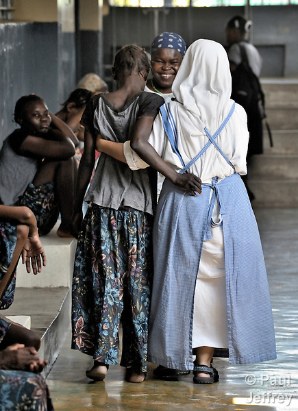 "At the ""House for the Dying"", a hospice for AIDS patients and other seriously ill patients run by the Sisters of Charity in Port au Prince, Haiti, Sister Paula, a Spanish nun, supports a patient as she walks."