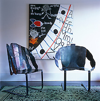 A pair of sculpted steel chairs with a painting by Los Angeles artist Elmo on the wall behind