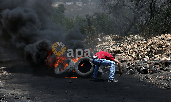 A Palestinian protester takes cover during clashes with Israeli security forces following a weekly demonstration against the expropriation of Palestinian land by Israel in the village of Kfar Qaddum, near Nablus, in the occupied West Bank on June 30, 2017. Photo by Ayman Ameen