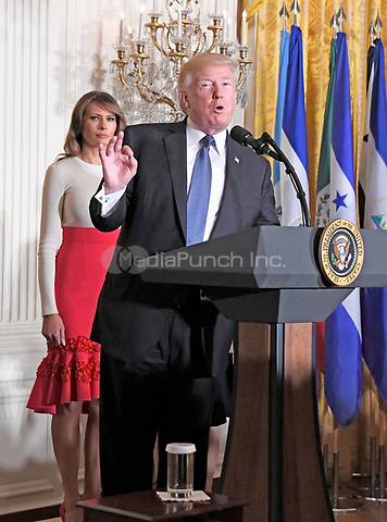 United States President Donald J. Trump makes remarks as he and first lady Melania Trump host a Hispanic Heritage Month event in the East Room of the White House in Washington, DC on Friday, October 6, 2017.  200 Hispanic business, community, and faith leaders, and guests from across the country have been invited to join in the celebration.  First lady Melania Trump looks on from left.<br /> Credit: Ron Sachs / CNP / MediaPunch