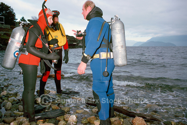 Scuba Divers wearing Oxygen Tanks / Diving Cylinders prepare for diving in Pacific Ocean, along the West Coast near Vancouver, BC, British Columbia, Canada