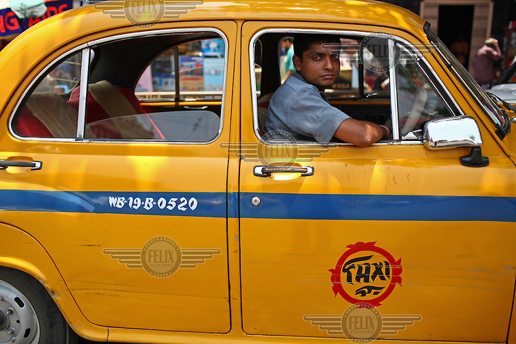 A yellow taxi cab driver waits in a traffic jam outside Howrah railway station in Kolkata.