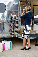 Attractive female shopper shops for new sunglasses at an Austin outdoor shopping mall