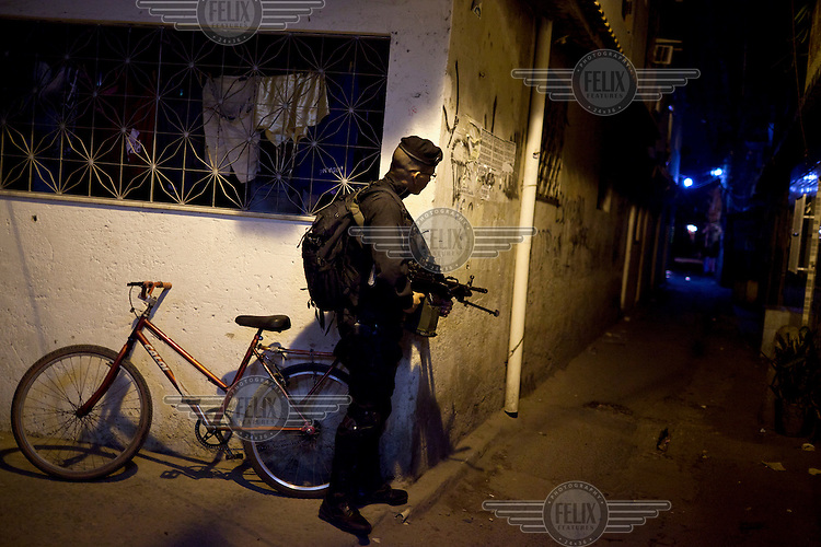 A heavily armed special police officer guards a street corner in Complexo da Mare near Rio de Janeiro's international airport. The favela consists of a complex of 16 communities, in the north zone of Rio de Janeiro. It is the largest complex of favelas, housing 130,000 residents. It is targeted for pacification as the city prepares for the 2014 World Cup and the 2016 Olympics.