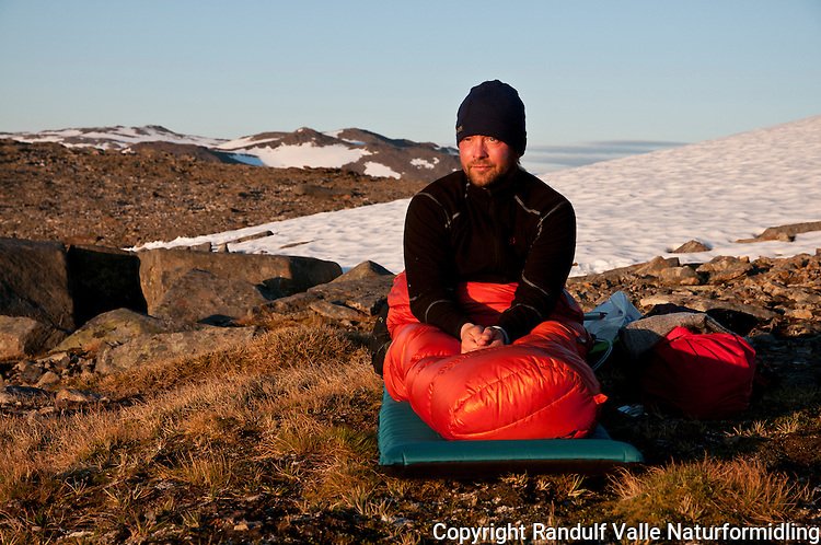 Mann i sovepose gjør seg klar til en natt under åpen himmel i høyfjellet på øya Seiland, rett ved fjellet Flasketind. ---- Person preparing for a night out on Seiland.