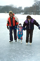 Family age 39 through 5 ice skating at Bracket Park. Minneapolis Minnesota USA
