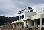 A tour bus remains atop a building in  Ogatsu, near Ishinomaki, Miyagi Prefecture, Japan on 01 Dec 2011. Photographer: Robert Gilhooly