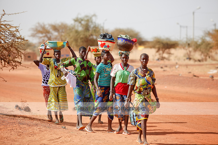 "In West Africa, certain villages have markets that ""assemble"" at regular intervals, such as weekly or every three days.  People from villages around the region converge on the town of Djibo in northern Burkina Faso every Wednesday to buy and sell food, livestock, and other goods and services.  Here women, arrive in Djibo on foot, carrying their wares on their heads in traditional African fashion."