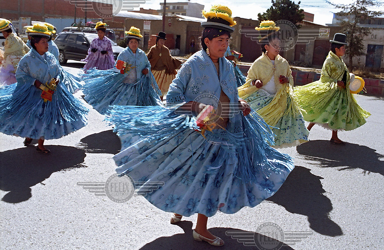 Cholitas, indigenous Bolivian women, dancing on the streets of La Paz as part of a fiesta celebrating Mother's Day.