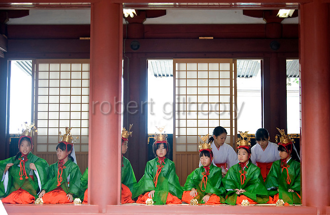 Yaotome dancers await their turn during a ritual inside the inner sanctuary during the annual Reitaisai Grand Festival at Tsurugaoka Hachimangu Shrine in Kamakura, Japan on  14 Sept. 2012.  Sept 14 marks the first day of the 3-day Reitaisai festival, which starts early in the morning when shrine priests and officials perform a purification ritual in the ocean during a rite known as hamaorisai and limaxes with a display of yabusame horseback archery. Photographer: Robert Gilhooly