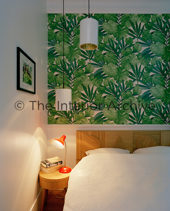 The bedroom has a signature wall of floral wallpaper and is furnished with a bed and headboard by The Hansen Family