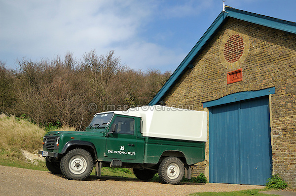 Green Land Rover Defender TD5 110 HCPU with white hardtop used by the National Trust on the White Cliffs of Dover UK 2005. In the background a pituresque barn with a blue door. --- No releases available. Automotive trademarks are the property of the trademark holder, authorization may be needed for some uses.