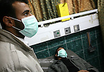 A Palestinian men wearing a protective masks crosses a street in Gaza City on December 6, 2009. Five people in the Hamas-run Gaza Strip were confirmed to have contracted swine flu, the first cases of the virus in the blockaded coastal enclave, officials said. In the occupied West Bank, at least 1,250 cases of swine flu have been reported, with nine deaths, according to government figures. Photo by Mohammed Othman