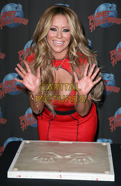 "AUBREY O'DAY.Aubrey O' Day visits Planet Hollywood in Times Square to promote her new Oxygen docu-series ""All About Aubrey"", New York, NY, USA..March 7th, 2011.half length black dress cut out cleavage hands palms plaster prints smiling red.CAP/ADM/PZ.©Paul Zimmerman/AdMedia/Capital Pictures."
