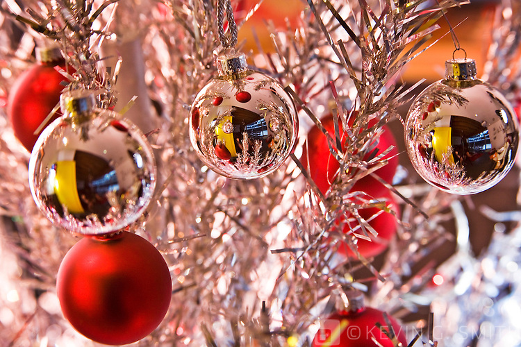 Close up of silver reflective and red glass ball Christmas ornaments hanging on 60's retro aluminum christmas tree.