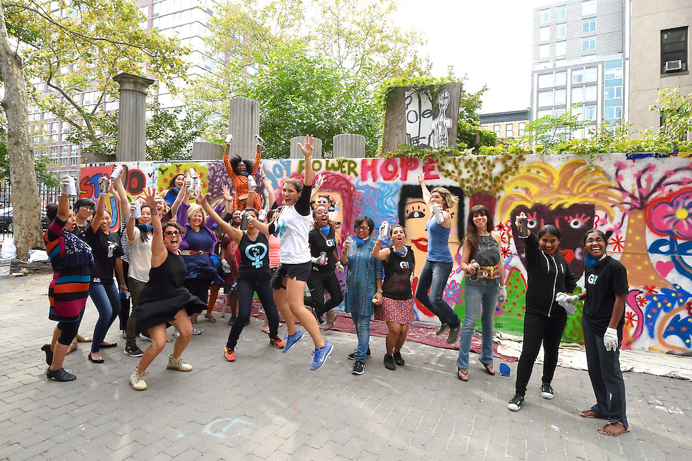 Group photo of the artists jumping for joy in front of their mural.