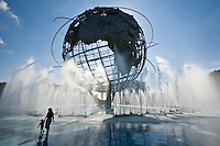 A mother and small child enjoying the spray from the water fountains at the Unisphere, also known as the Globitron, in Flushing Meadows Park, in the borough of Queens, New York City on a bright sunny afternoon. Originally built in April 1964 for the New York World's Fair, it is currently the site of the U.S. Open tennis championship.