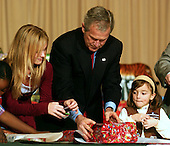 Washington, D.C. - December 22, 2006 -- United States President George W. Bush helps wrap Christmas gifts destined for injured soldiers and their families who are staying at the Mologne House at the Walter Reed Army Medical Center in Washington, D.C. on Friday, December 22, 2006.<br /> Credit: Ron Sachs - Pool via CNP