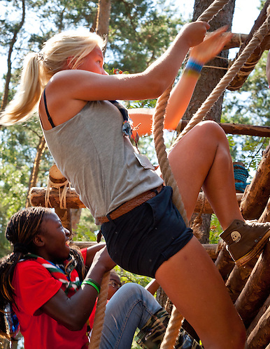African and European Girl climbing a wooden wall by a rope. Photo: André Jörg/ Scouterna