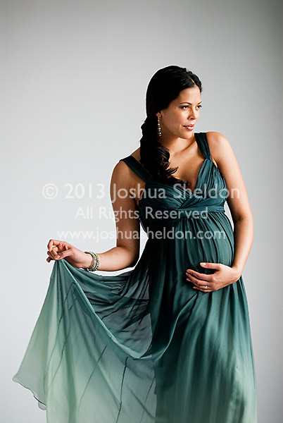 Pregnant Hispanic woman, hands on stomach