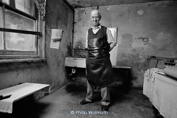 Charles King worked as a cobbler in the basement of 100 Walterton Road from 1935 until he retired in 1998.  His father had bought the business for £14 a century earlier, in 1898, and Charles was born above the shop in 1917.  Walterton Estate, North Paddington, 1992.