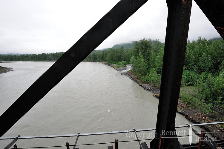 An Alaska Railroad bridge outlines the location where Gold Creek pours into the Susitna River north of Talkeetna, Alaska. The Alaska Railroad's Hurricane Turn is one of America's last true whistlestop trains.