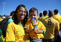 A young Brazil fan and his mother soak up the atmosphere outside the Itaquerao stadium ahead of kick off in the opening match of the 2014 World Cup vs Croatia