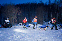 Norwegian exchange students and the official Takotna Parking Crew lead Jerry Sousa out as he leaves from his 24 hour layover at daybreak in 15 below temps during the 2010 Iditarod