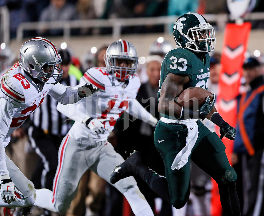 Michigan State Spartans running back Jeremy Langford (33) runs for a touchdown ahead of Ohio State Buckeyes safety Tyvis Powell (23) and cornerback Eli Apple (13)during the first quarter of the NCAA football game at Spartan Stadium in East Lansing, Michigan on Nov. 8, 2014. (Adam Cairns / The Columbus Dispatch)