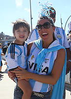 A young Argentina supporter and his mother make their way to the Maracana Stadium before kick off