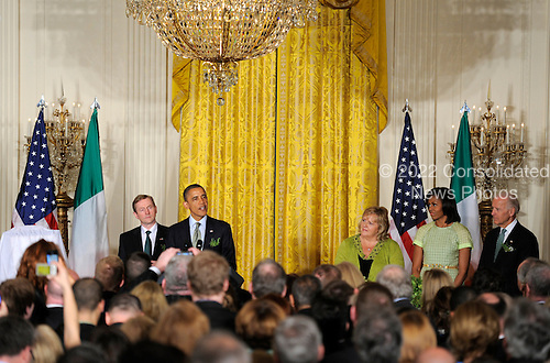 United States President Barack Obama (2nd,L) makes remarks as Irish Prime Minister Enda Kenny (L) listens along with first lady Michelle Obama (2nd,R), Kenny's wife Fionnuala (3rd,R) and Vice President Joe Biden (R) during a reception in the East Room of the White House, March 20, 2012, in Washington, DC. The two leaders concluded a working day devoted to discussions on economic matters, Ireland's peace keeping participations and foreign policy issues like Syria and Iran..Credit: Mike Theiler / Pool via CNP