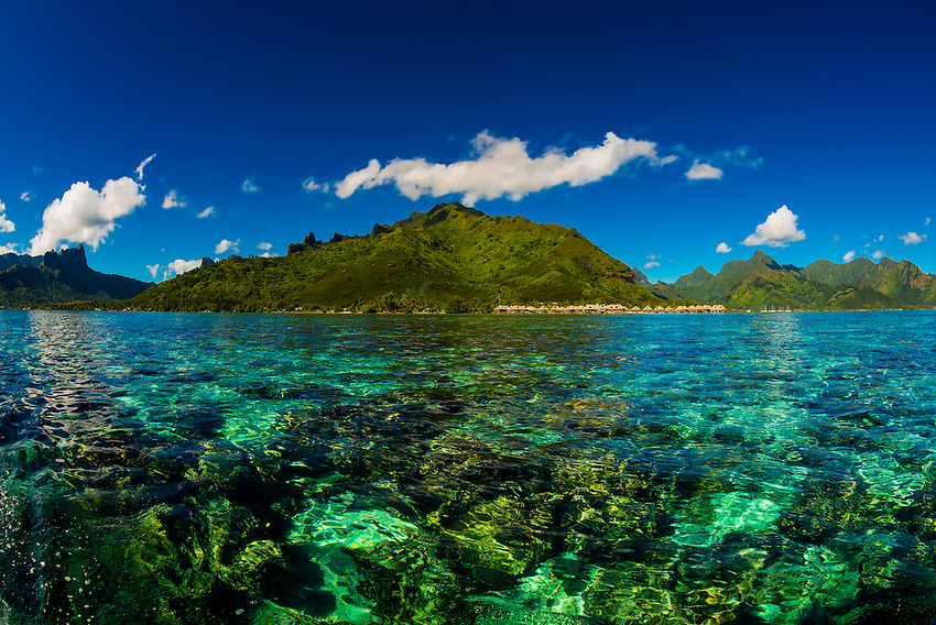 The lagoon inside the reef, with overwater bungalows at Hilton Moorea Lagoon Resort in background, island of Moorea, French Polynesia.