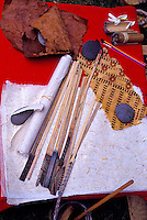 Tapa supplies, including carved wooden sticks dipped in paint and used to press designs into the cloth.