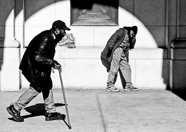 A man with a cane walks past Union Station as a second man rests against the wall on Feb. 6, 2009.