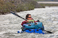 Ali blechman paddles in a pack raft on the Marsh Fork of the Canning River, Arctic National Wildlife Refuge, Brooks Range mountains, Alaska.