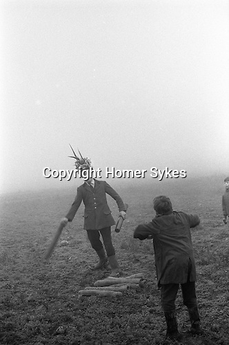 The Haxey Hood Game,<br /> Haxey, Humberside 6 January 1972<br /> <br /> <br /> The Chief Boggin Arthur Clark throws up one of the twelve childrens sack cloth hoods in Upper Thorpe Field on the boundary of Westwoodside and Haxey (the Hoodlands field no longer exists). There twelve sack hoods are thrown up. These are known as children's hoods since twenty pence is given to any boy or girl who gets one to either of the two pubs in Haxey, or to the Carpenter's Arms in Westwoodside, without being stopped by a Boggin. If he is stopped, the hood goes back to the start to be thrown up again.<br /> <br /> At about four o'clock a leather hood is thrown up, and a scrum known as the 'sway' forms round it. The teams of men, who can come from anywhere, push against each other trying to get the hood to their favourite pub. Usually several hours pass before the hood reaches a goal, and when it does drinks are on the house. The hood stays in the pub until the following New Year's Eve when it is redeemed by the boggin the pubs in the area to drum up interest in the game.
