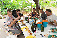 Daniel Le Conte des Floris at a working lunch with the bottling line persons. Domaine Le Conte des Floris, Caux. Pezenas region. Languedoc. In the garden. Lunching with the bottling team. Owner winemaker. France. Europe.