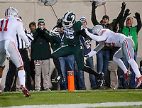 Michigan State Spartans wide receiver Keith Mumphery (25) leaps into the end zone past Ohio State Buckeyes cornerback Doran Grant (12) during the first quarter of the NCAA football game at Spartan Stadium in East Lansing, Michigan on Nov. 8, 2014. (Adam Cairns / The Columbus Dispatch)
