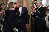 Director of National Intelligence Dan Coats (C), with United States Vice President Mike Pence (R) looking on, kisses his wife Marsha Coats (L) during a swearing in ceremony in the US Capitol in Washington, DC, USA, 16 March 2017.<br /> Credit: Shawn Thew / Pool via CNP