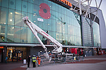 "© Joel Goodman - 07973 332324 . 7 November 2013 . Sir Matt Busby Way , Manchester , UK . A poppy stencilled on to the front of Manchester United 's stadium at Old Trafford today , 7th November 2013 , as viewed from Sir Matt Busby Way complete with broken cherry picker which has delayed the stencilling of a message , believed to be "" We will never forget "" . Photo credit : Joel Goodman"