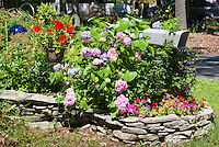 Planting flowers and vines around a mailbox with stone wall raied bed, gazing ball, driveway,hammock, hydrangea, impatins, hanging container pot of red geraniums, antique car convertible. Curb Appeal landscaping