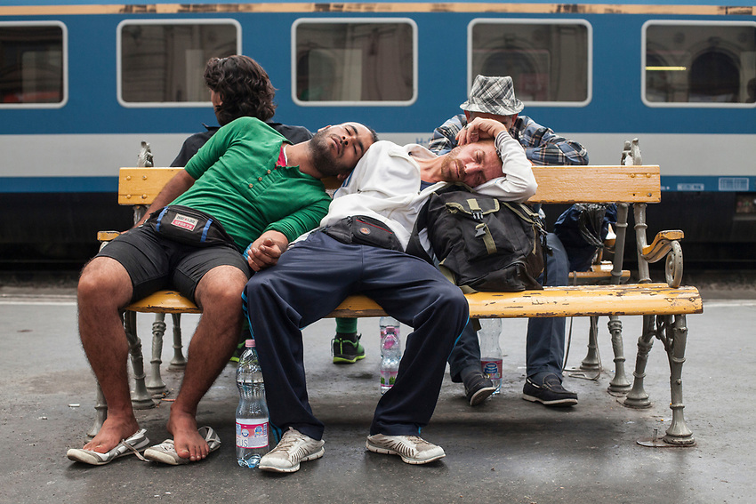 Refugees sleeping on a train station bench while waiting for a train to take them to Germany. Mostly Syrian refugees seek rest while waiting for trains to take them away to destinations around Europe. The Hungarian government closed the station and then reopened but cancelled all international trains. Budapest Keleti railway station  is the main international and inter-city railway terminal in Budapest, Hungary.