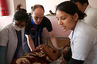 Dr Stephen Reaney, a GP doctor from Northern Ireland, helps assess and treat a Nepalese woman with spinal injuries, in a specialist clinic just outside Kathmandu.<br /> <br /> Stephen is part of the UK's International Emergency Trauma Register, a volunteering scheme run by the NHS with funding from the Department for International Development. The register allows specially trained NHS medical professionals to be deployed from the UK to other countries in times of need, to help respond to humanitarian emergencies. The medics are deployed as part of the UK's Emergency Medical Team (UK EMT), which is also funded by the UK government through the Department for International Development.<br /> <br /> The 30-person UK EMT was deployed to Nepal on 26 April 2015, after the government of Nepal requested international assistance to help it respond to the 7.8 magnitude earthquake which struck the country on 25 April. The team was deployed alongside the 60-person UK International Search and Rescue Team, which is comprised of specialist urban search and rescue firefighter teams from fire &amp; rescue services around the UK.<br /> <br /> <br /> Picture: Russell Watkins/DFID