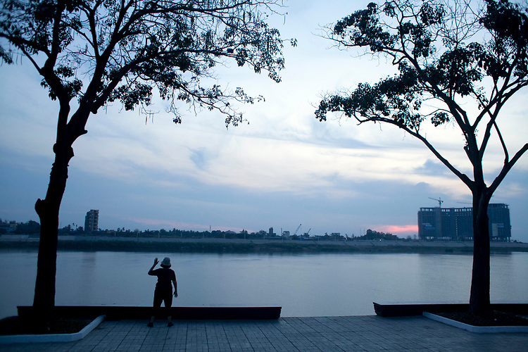A woman does morning exercises on the Mekong River in Phnom Penh, Cambodia. <br /> <br /> Photos &copy; Dennis Drenner 2013.