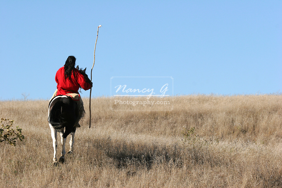 A Native American Indian man riding away on horseback on an Indian horse up a hill on the prairie of South Dakota