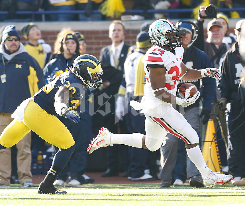 Ohio State Buckeyes running back Carlos Hyde (34) races down the Michigan sideline and past Michigan Wolverines safety Thomas Gordon (30) for a gain in second half action at Michigan Stadium Ann Arbor, MI on November 30, 2013.  (Chris Russell/Dispatch Photo)